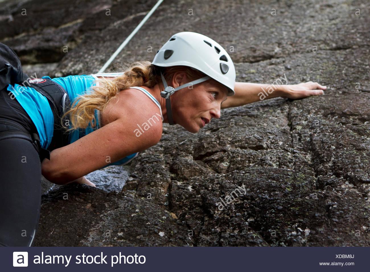 Sweden, Ostergotland, Vaderstad, Woman climbing rock - Stock Image