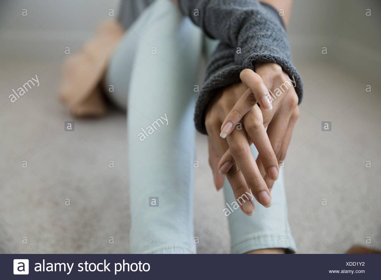 Close up young woman with hands clasped - Stock Image
