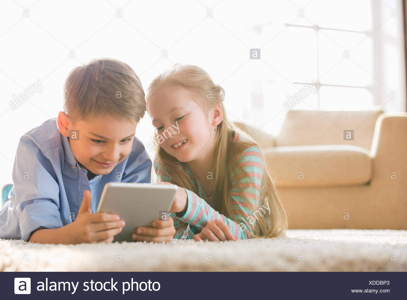 Brother and sister using digital tablet on floor at home - Stock Image