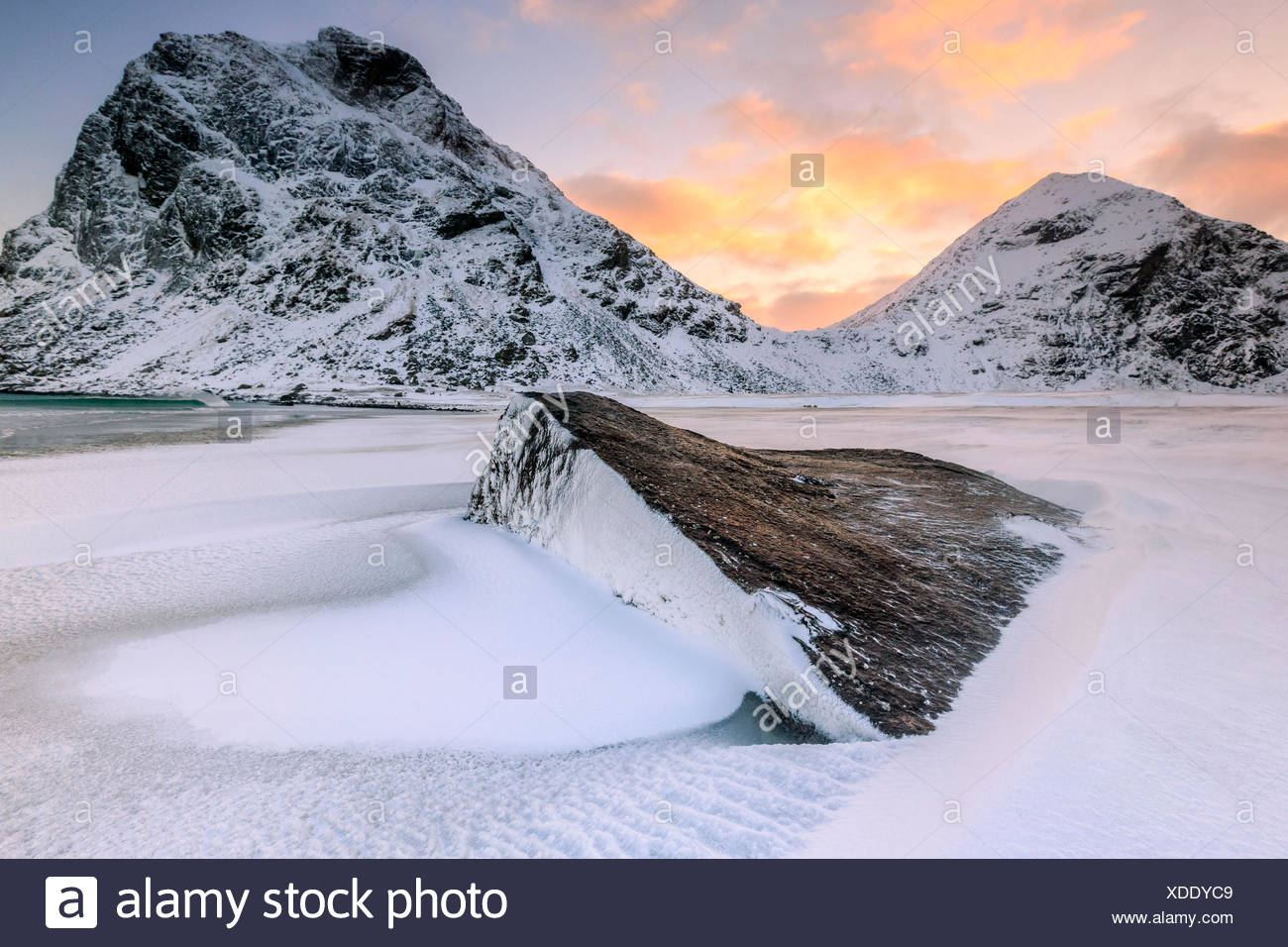 Dawn illuminates the rocks shaped by wind surrounded by fresh snow, Uttakleiv Lofoten Islands Norway Europe - Stock Image