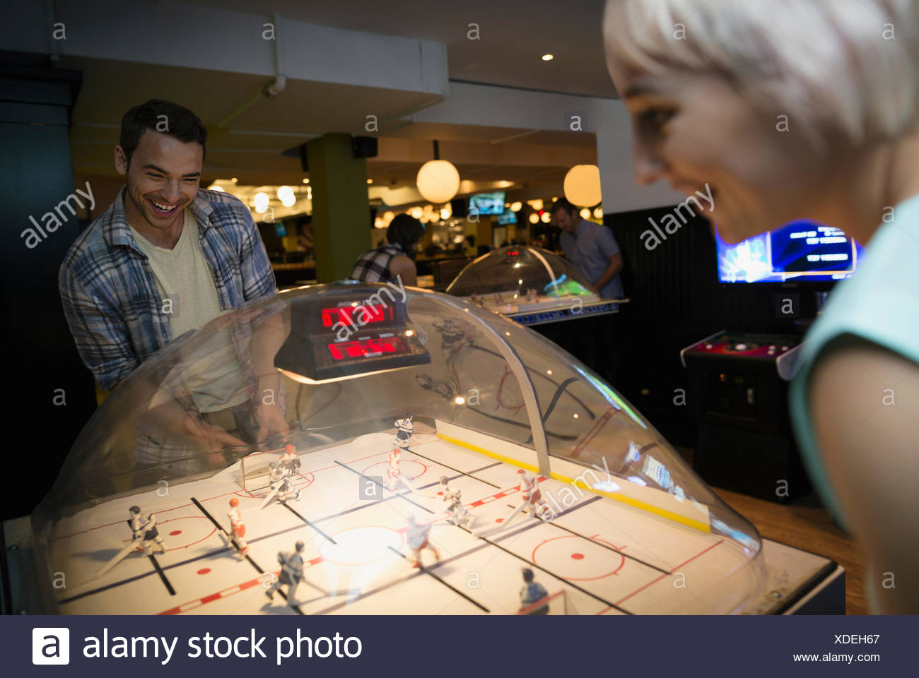 Friends playing bubble hockey game at bowling alley - Stock Image