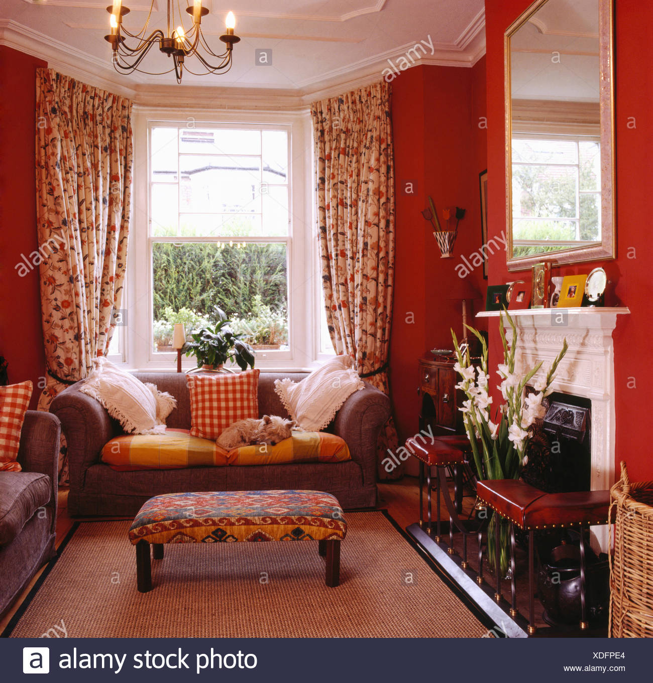 Upholstered Stool And Grey Sofa In Front Of Window With Floral Curtains In  Red Eighties Living Room