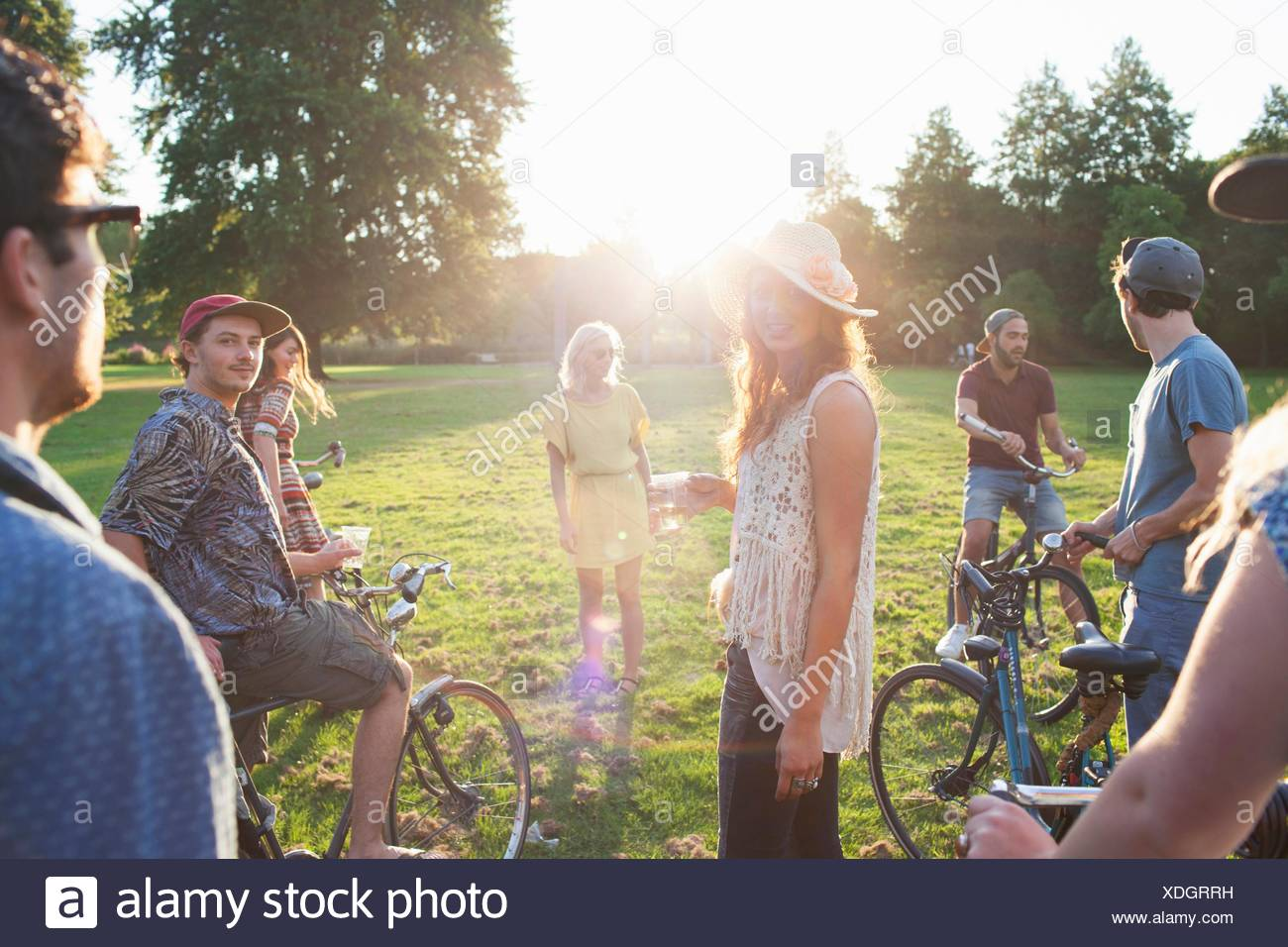 Group of party going adults arriving in park on bicycles at sunset - Stock Image