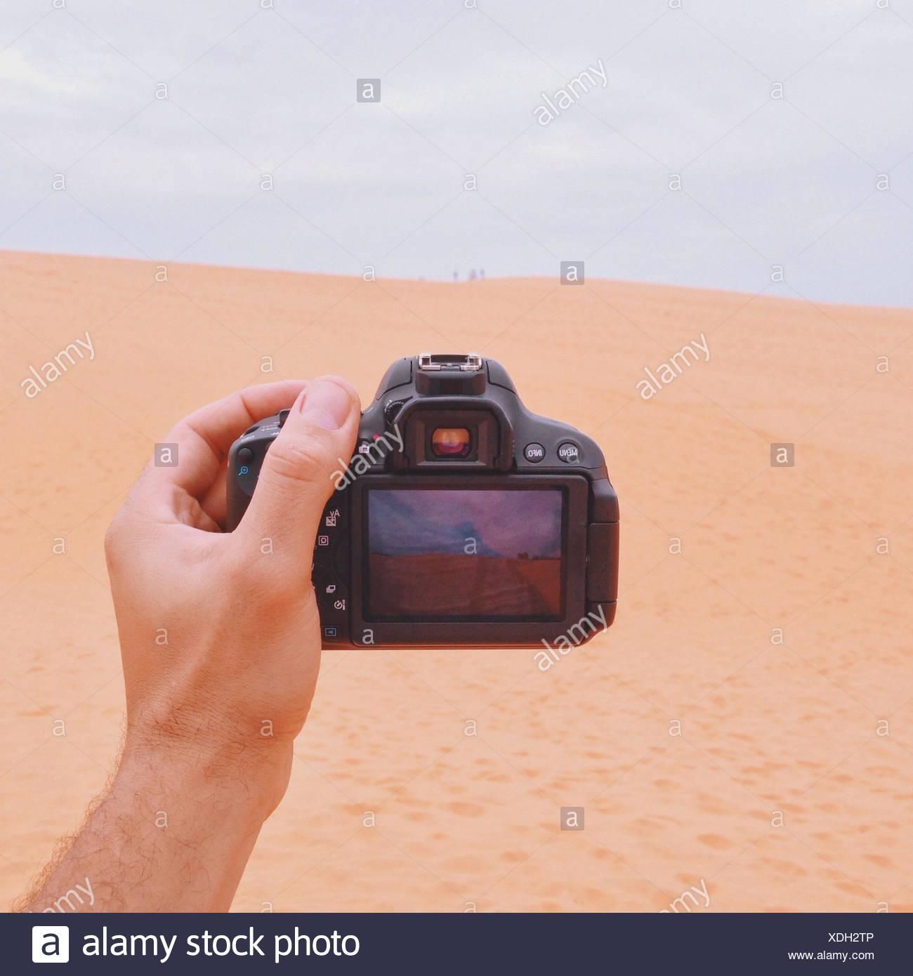 Man holding camera - Stock Image