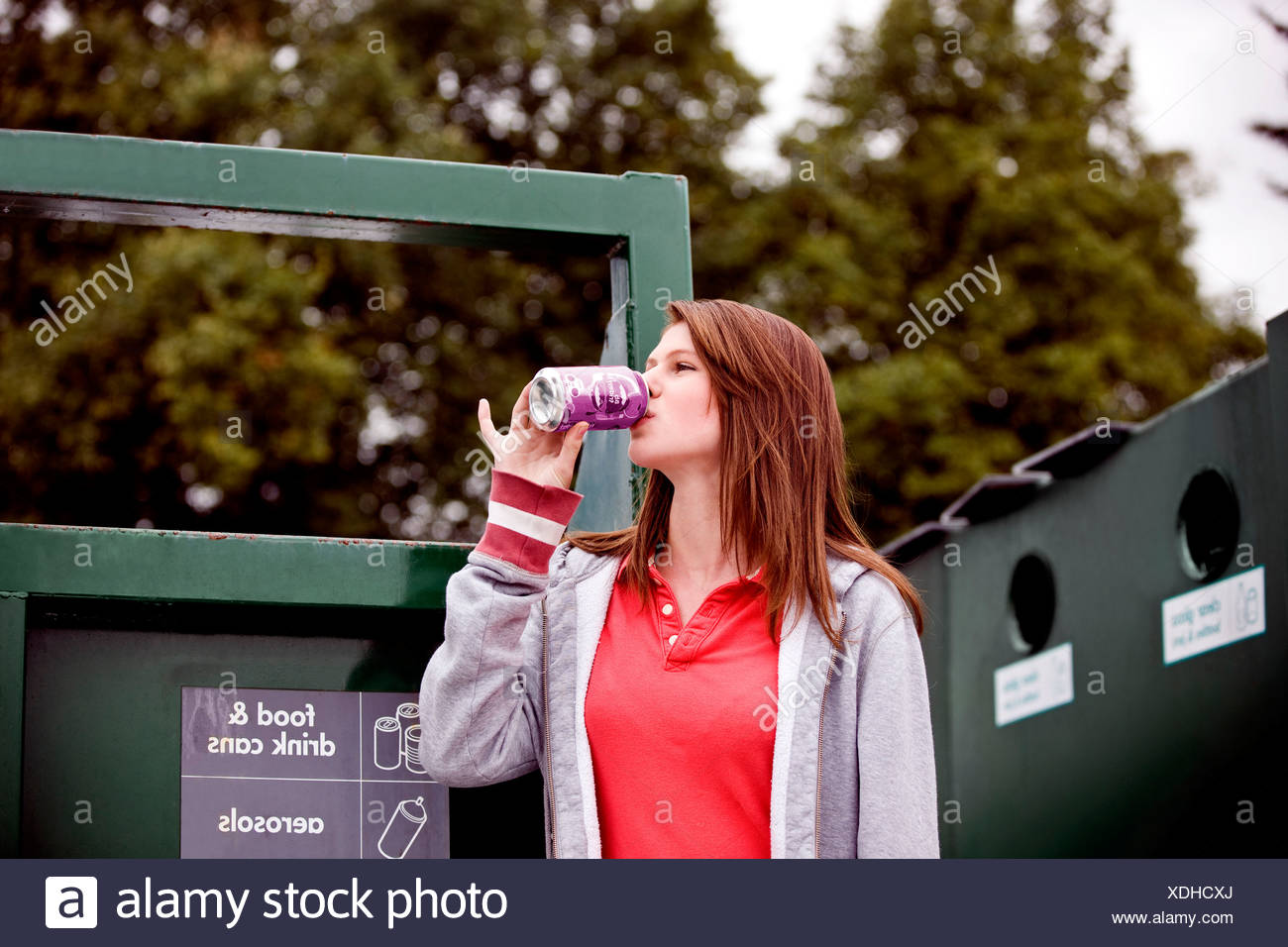 A teenage girl drinking a soft drink in a recycling center - Stock Image