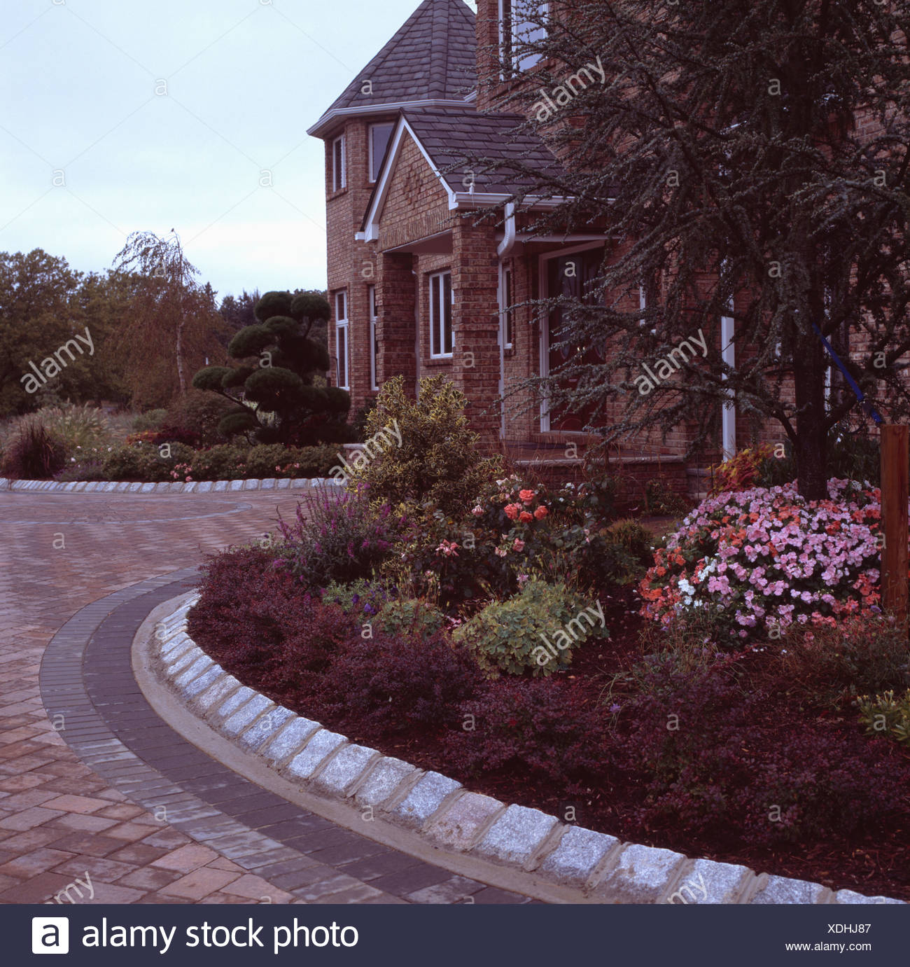 Stone Edging Around Curved Garden Border In Front Of Traditional New Build  House In Early Evening