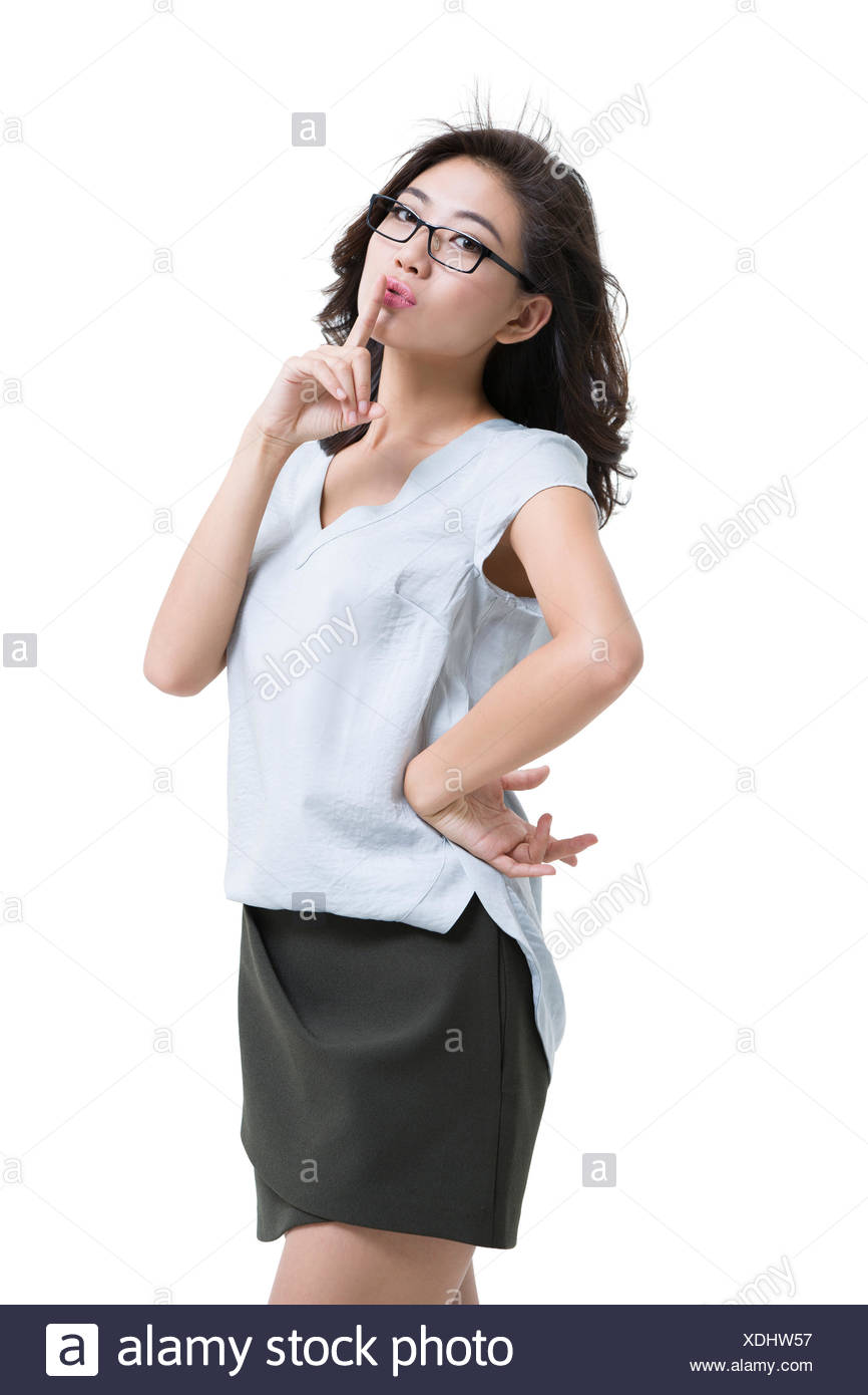 Happy young woman with finger on lips - Stock Image