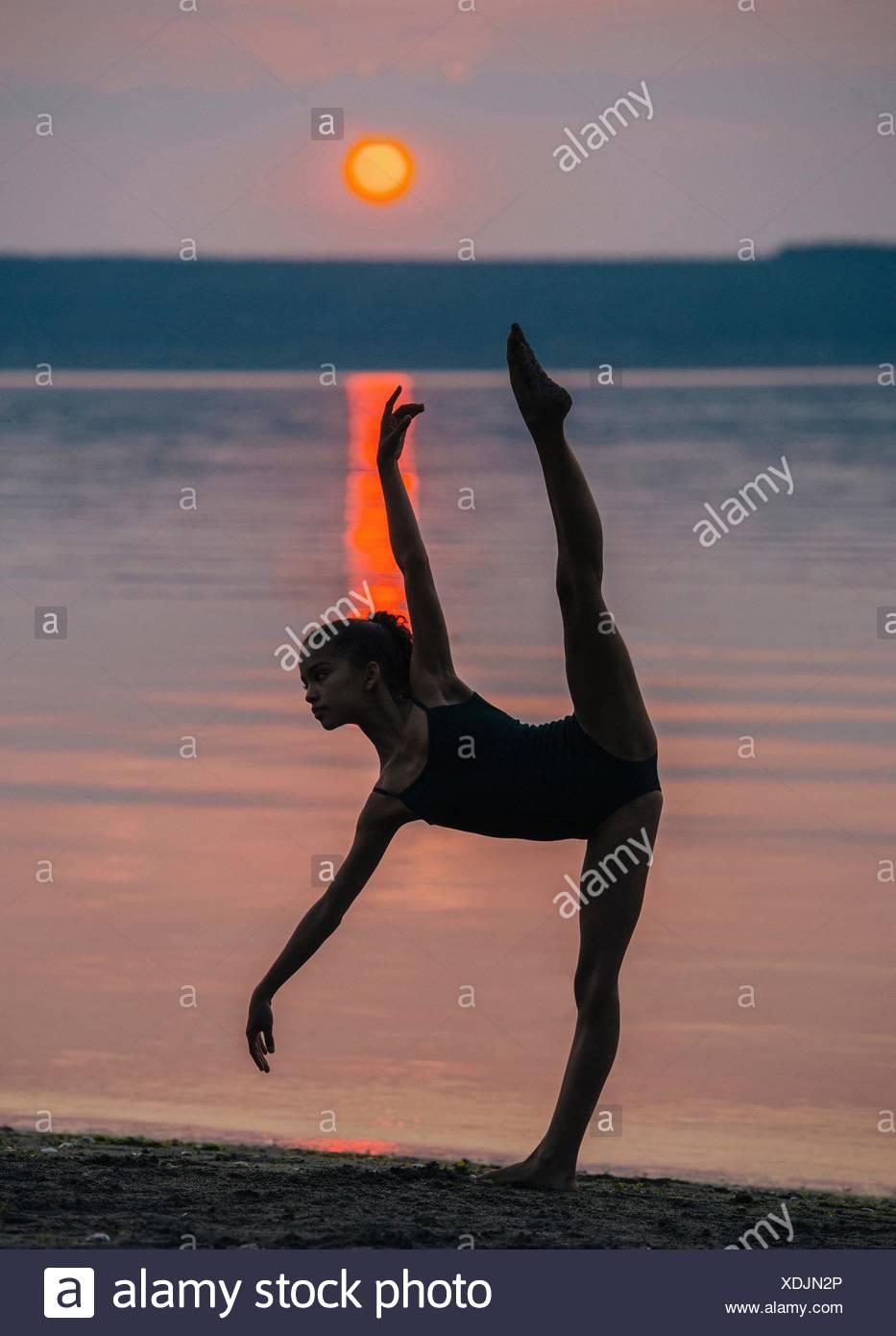 Girl by ocean at sunset on one leg, bending forward arm and leg raised - Stock Image