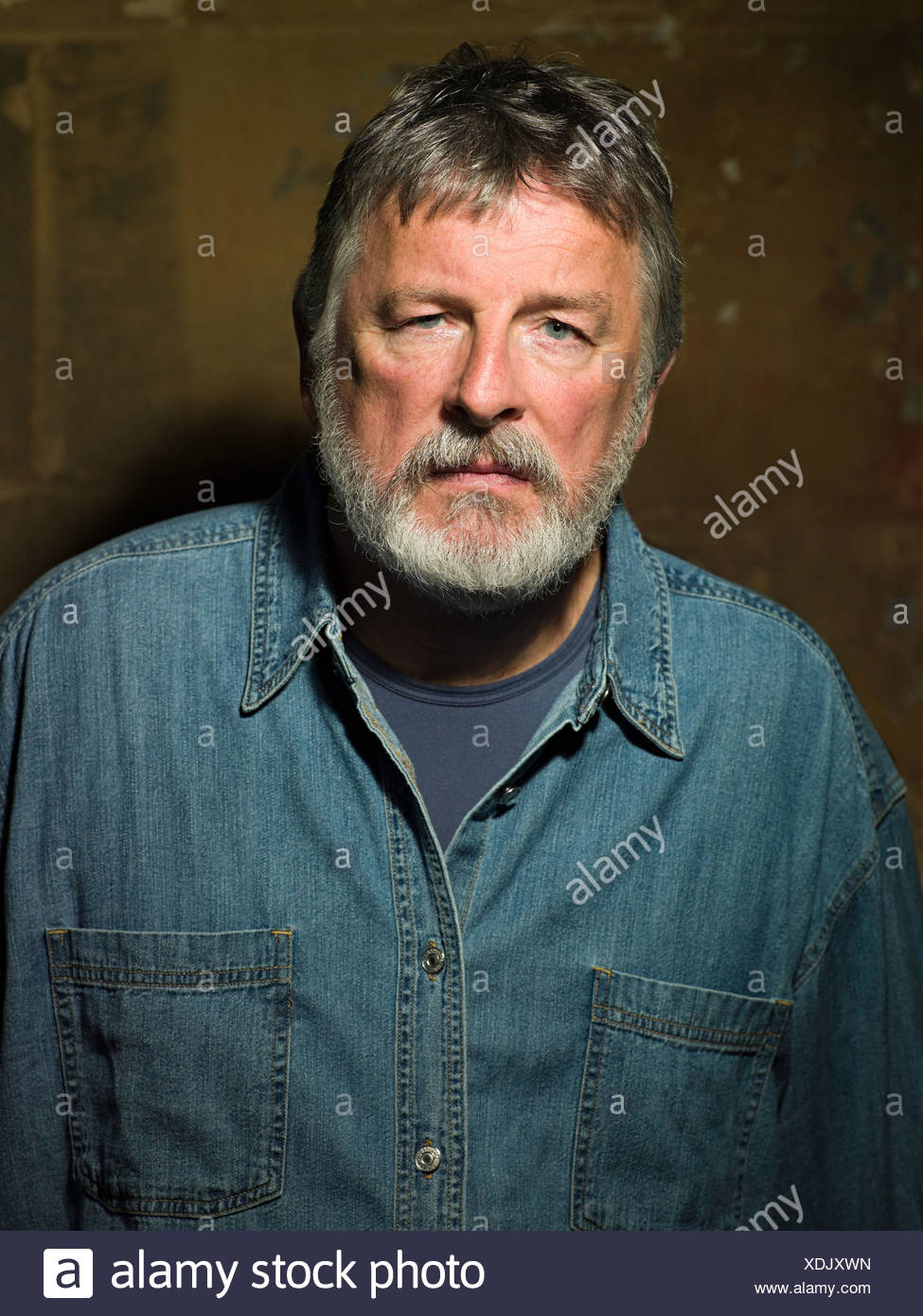 Mature man wearing a denim shirt - Stock Image