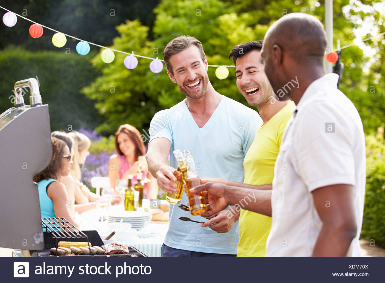 Group Of Men Cooking On Barbeque At Home - Stock Image