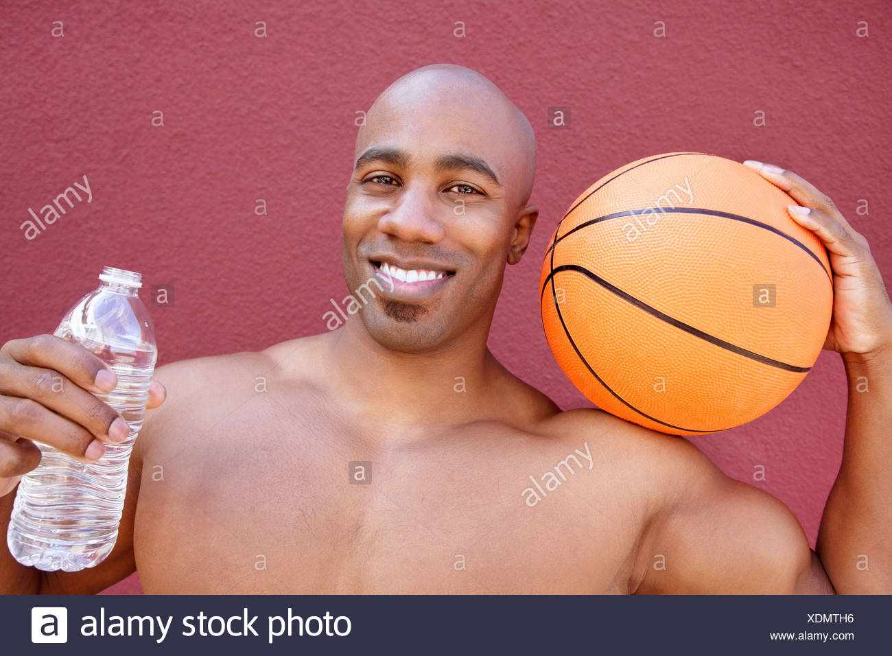 Portrait of an African American athlete with basketball and water bottle over colored background - Stock Image