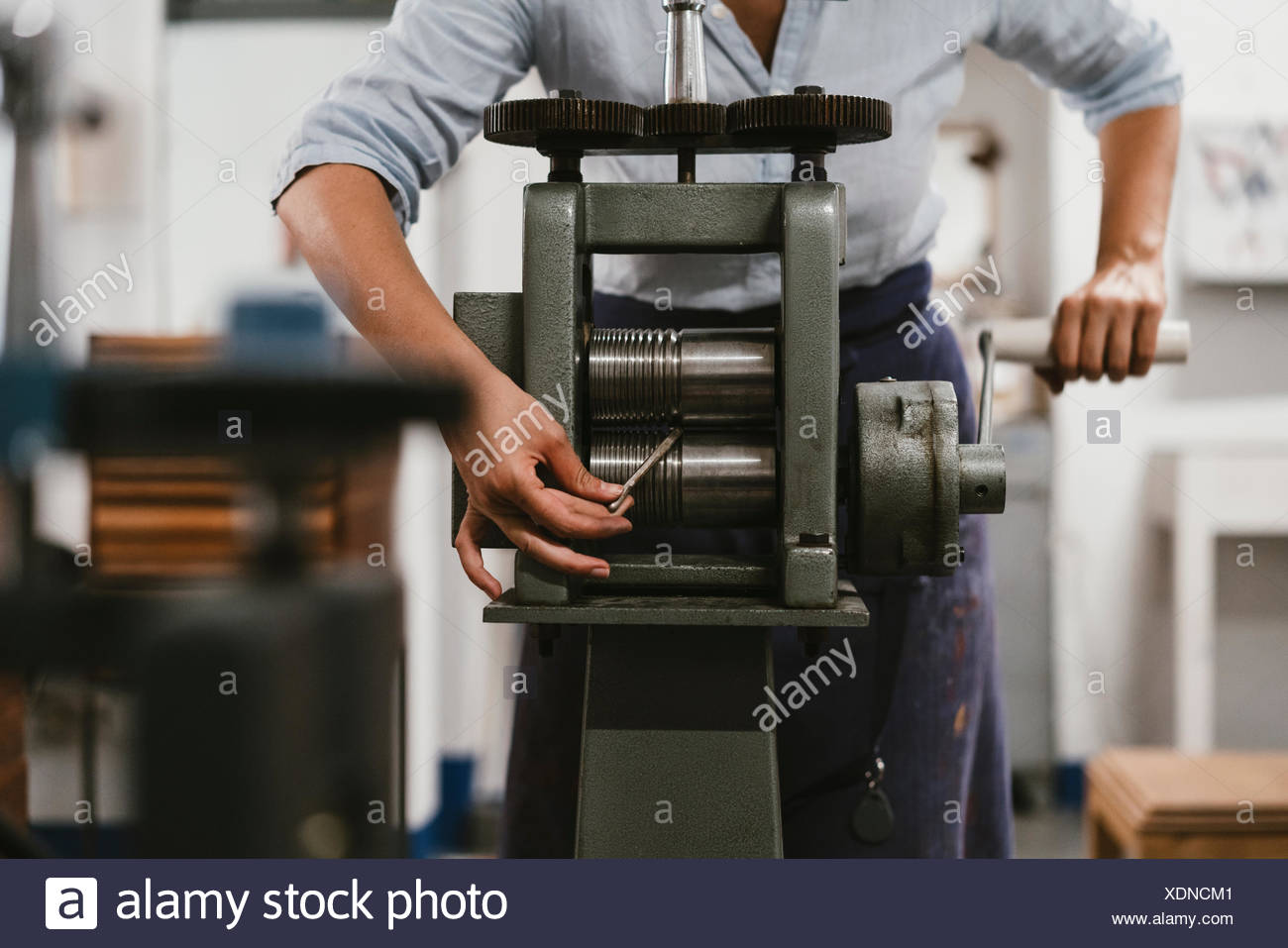 Mid section of female jeweller winding metal rod through machine in jewellery workshop - Stock Image