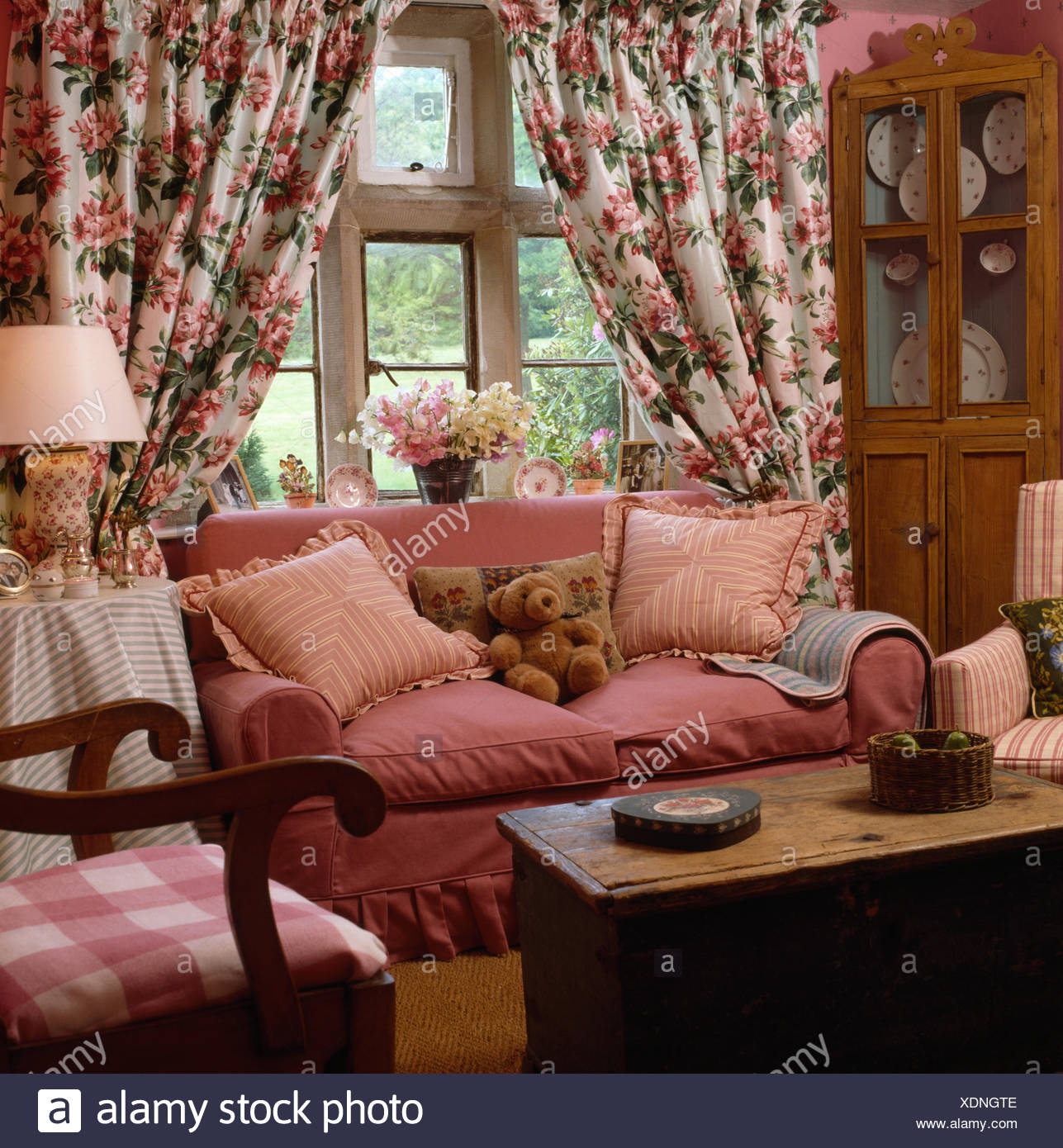 Floral Curtains On Window Behind A Pink Sofa In Country Living Room