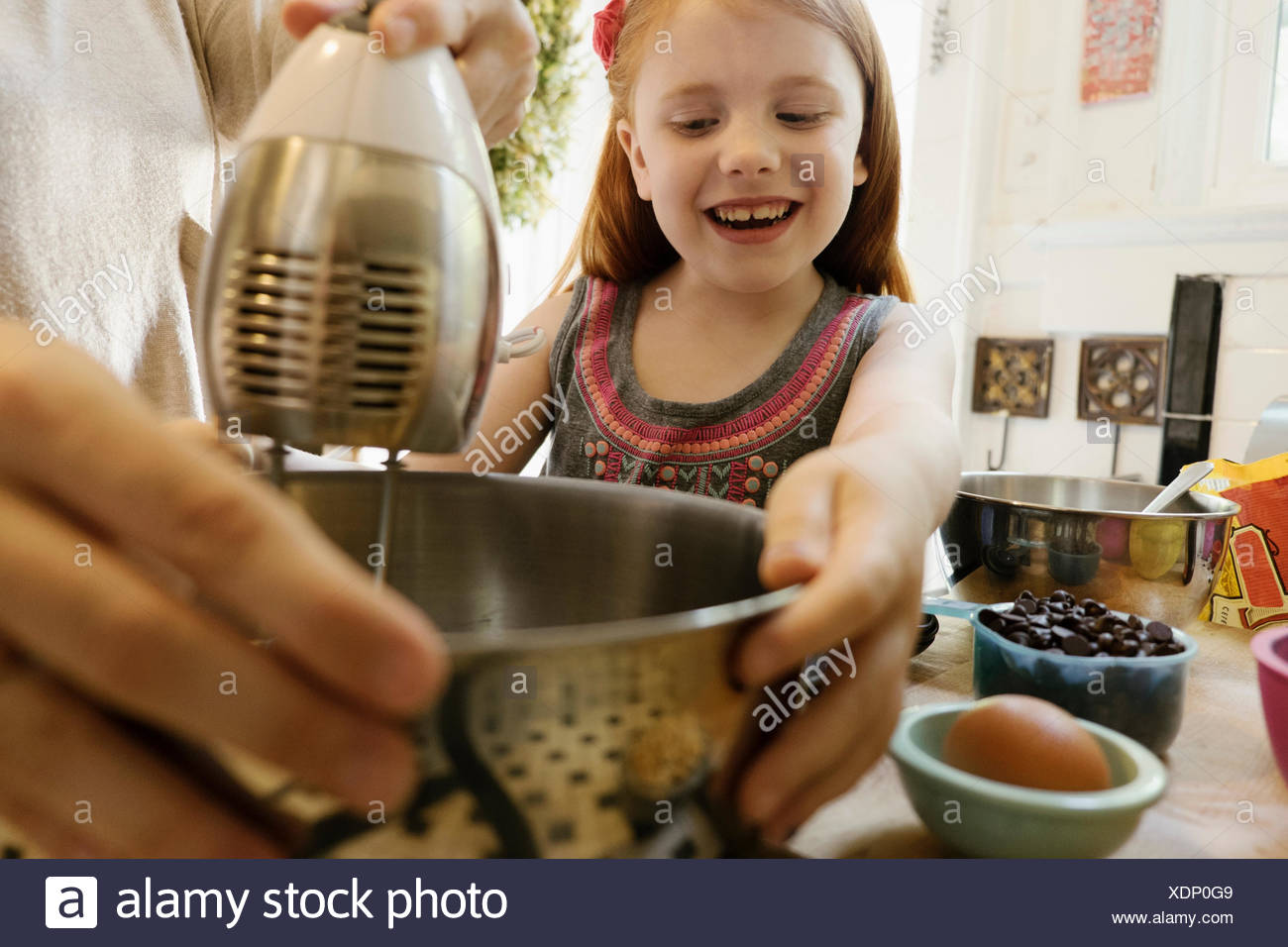 Girl giving mother a helping hand in kitchen - Stock Image