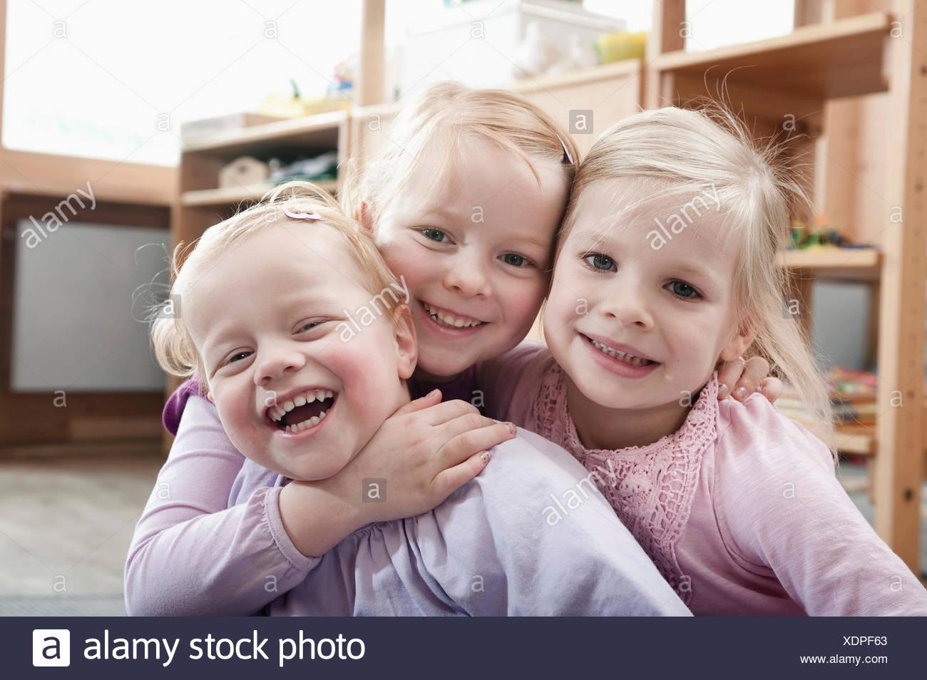 Three little girls, best friends, in kindergarten - Stock Image