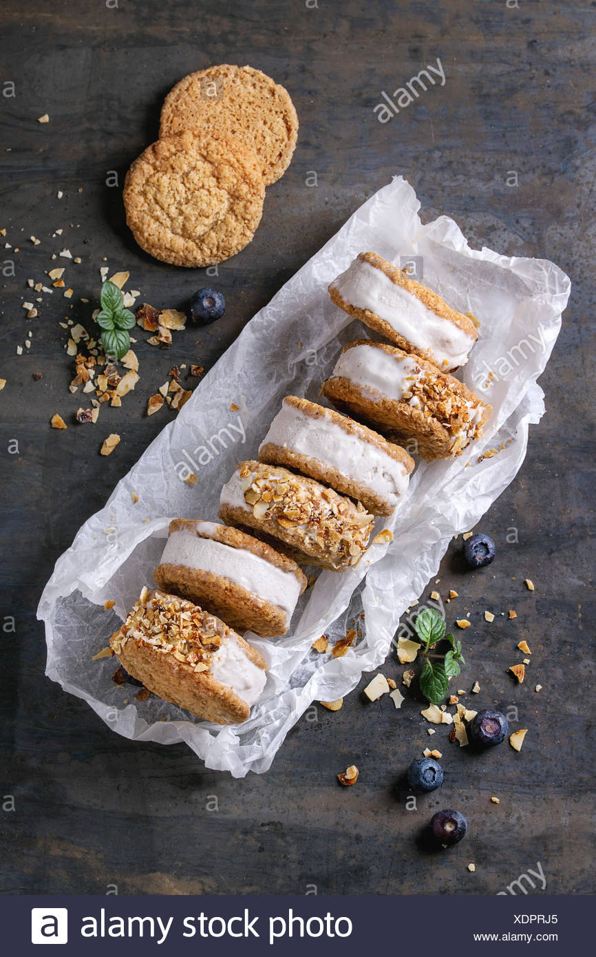 Set of homemade ice cream sandwiches in oat cookies with almond sugar crumbs, blueberries and mint on baking paper over dark metal texture background. - Stock Image