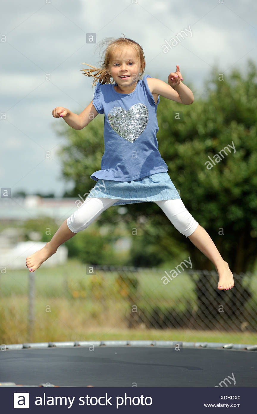 Italia, Calabria, Girl (2-3) jumping on trampoline in summer - Stock Image