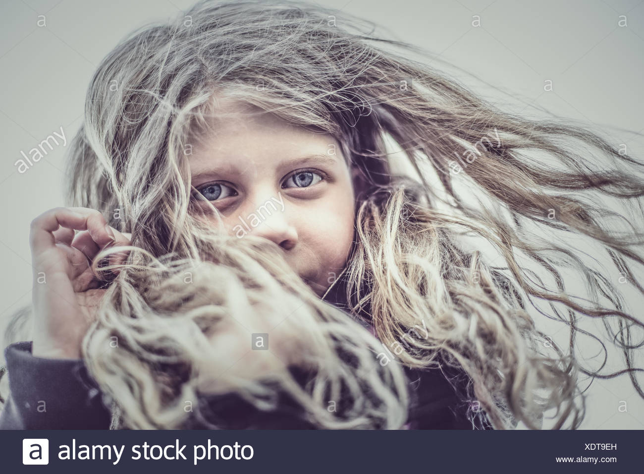 Portrait of girl (8-9) with hair blowing in wind - Stock Image