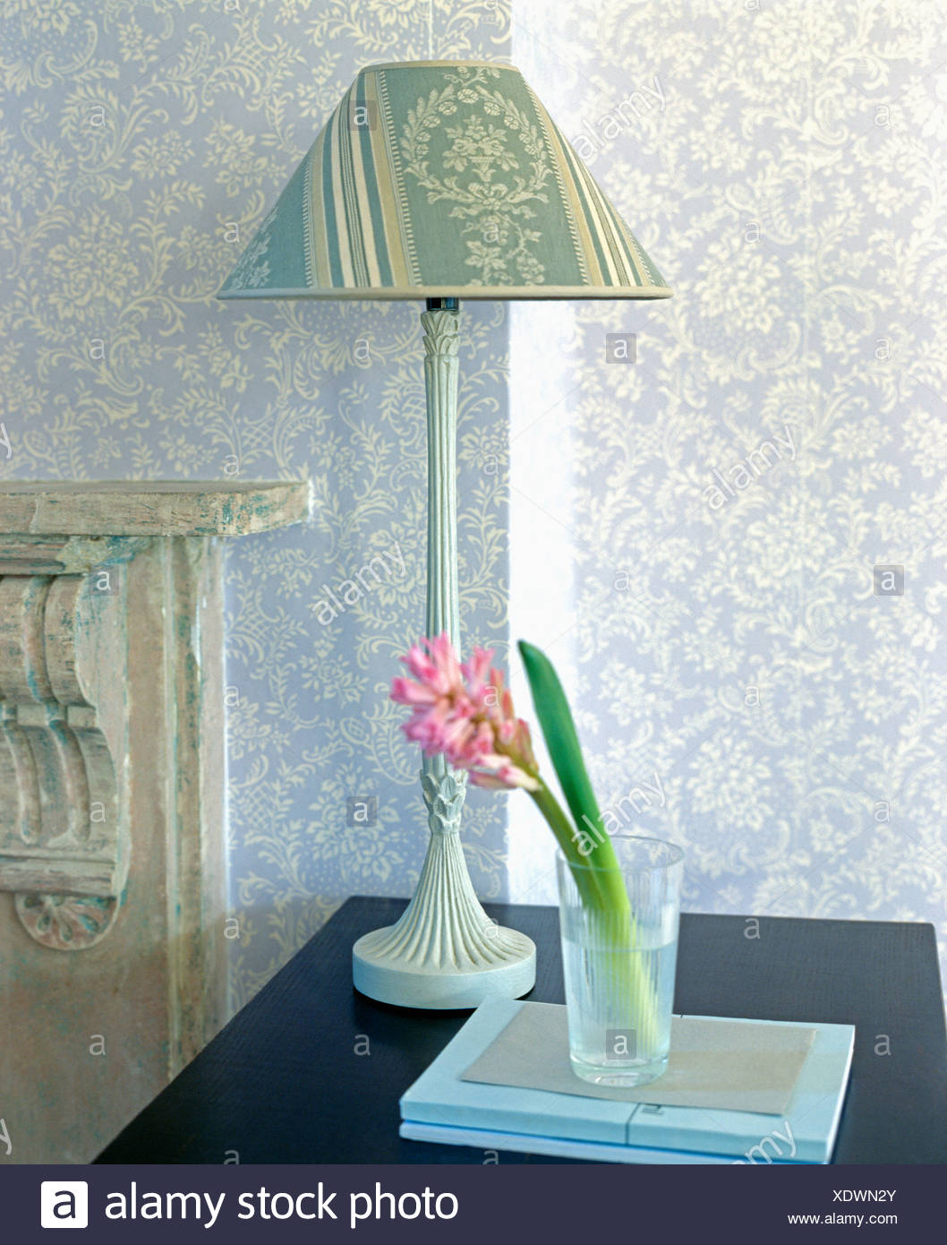 Close up of lamp with patterned lampshade on table with pink close up of lamp with patterned lampshade on table with pink hyacinth in glass vase aloadofball Choice Image