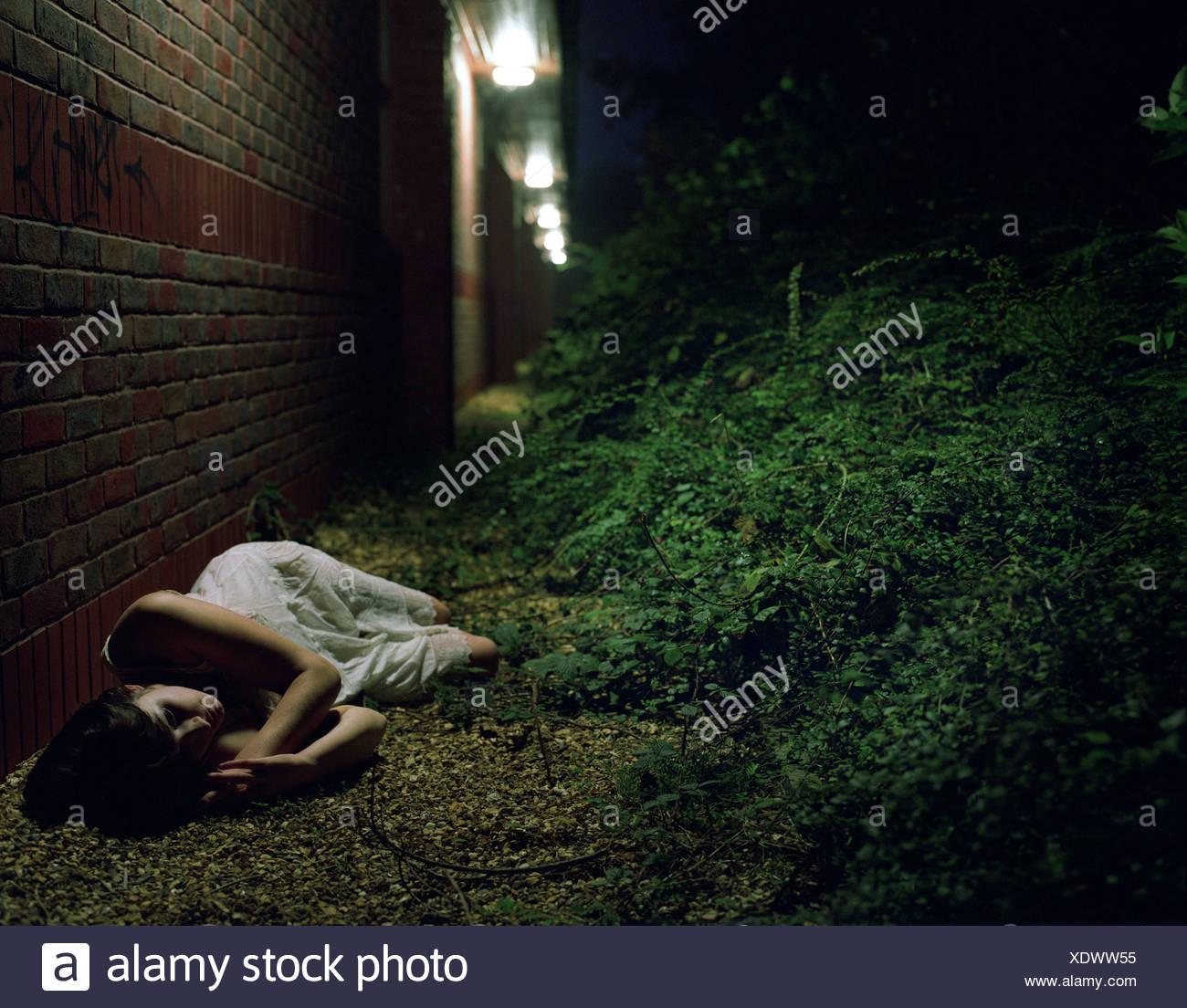 Woman lying by brick wall at night - Stock Image
