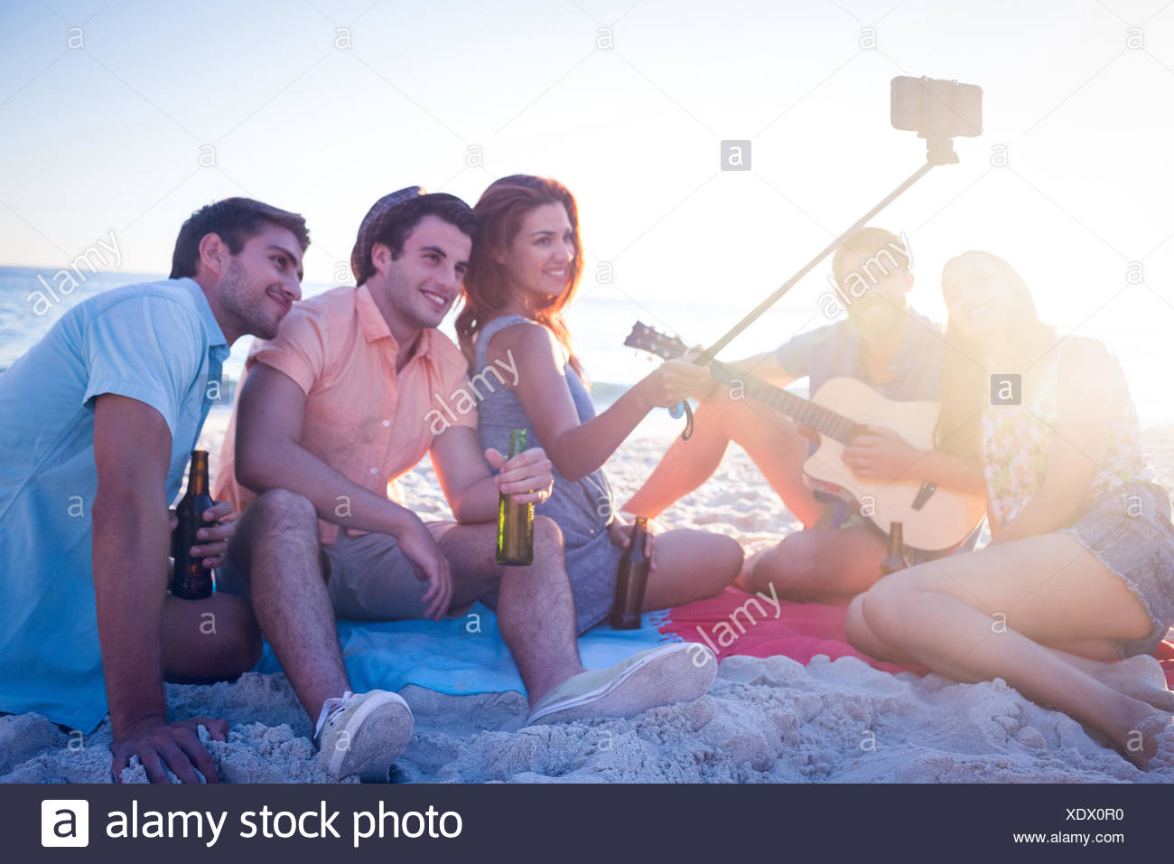 Happy hipsters taking pictures with selfie stick - Stock Image