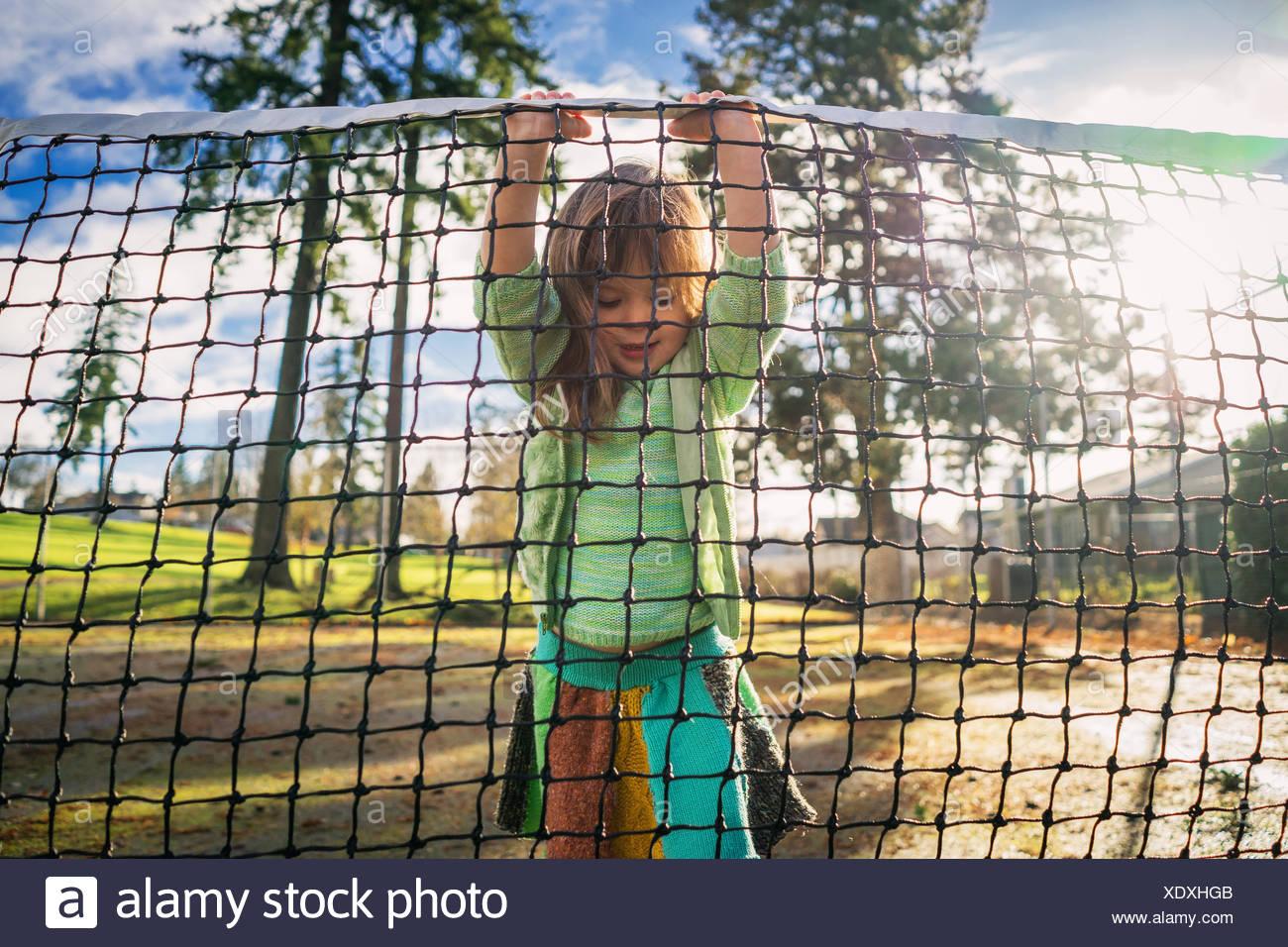 Girl standing on tennis court lifting net - Stock Image