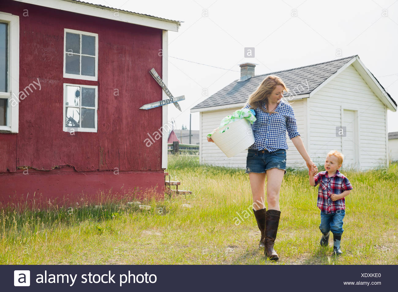 Mother and son carrying laundry outside house - Stock Image