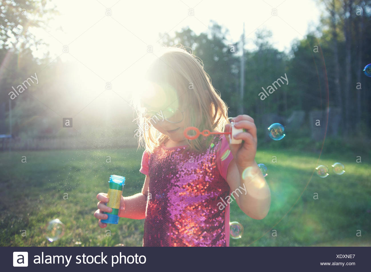 Girl blowing bubbles in garden - Stock Image