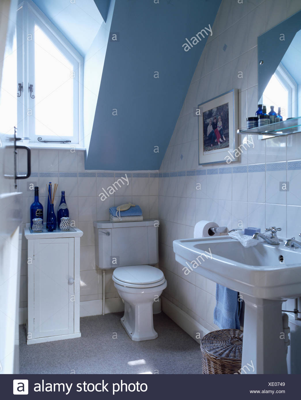 white pedestal basin and toilet in blue attic bathroom with small