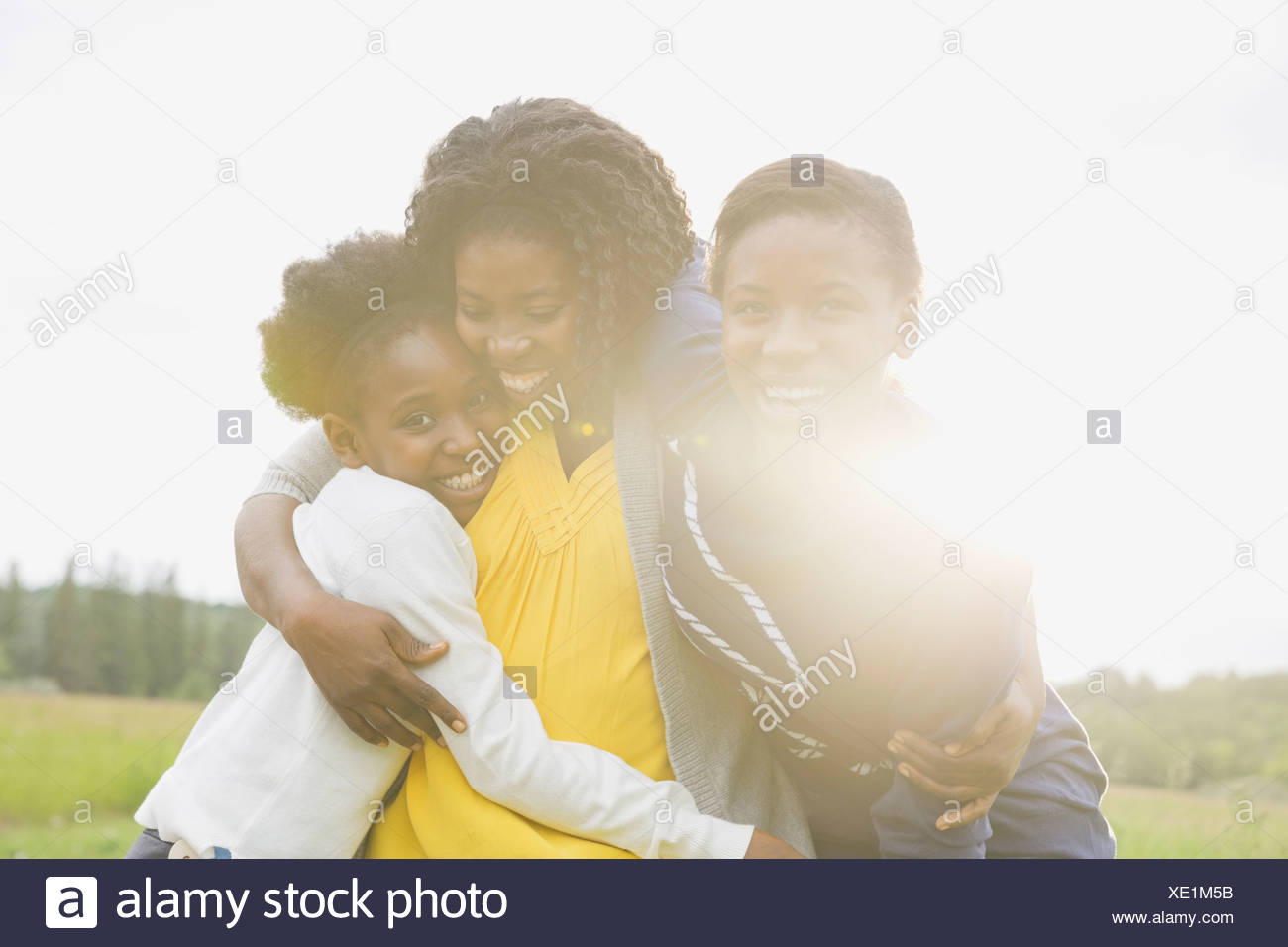 Cheerful mother and daughters hugging outside - Stock Image