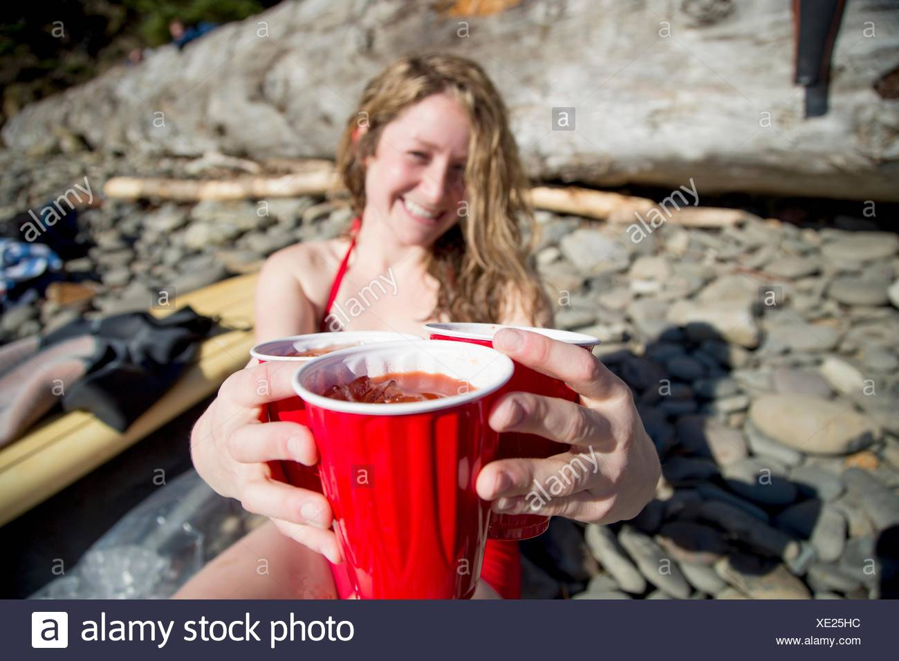 Young woman sitting on rocky beach, holding drinks, smiling, Short Sands Beach, Oregon, USA - Stock Image