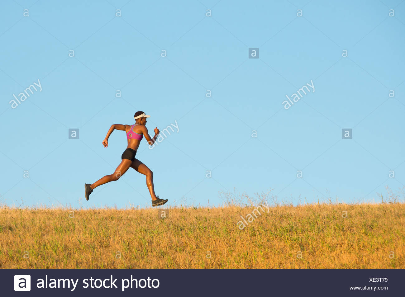 Young woman running across field - Stock Image