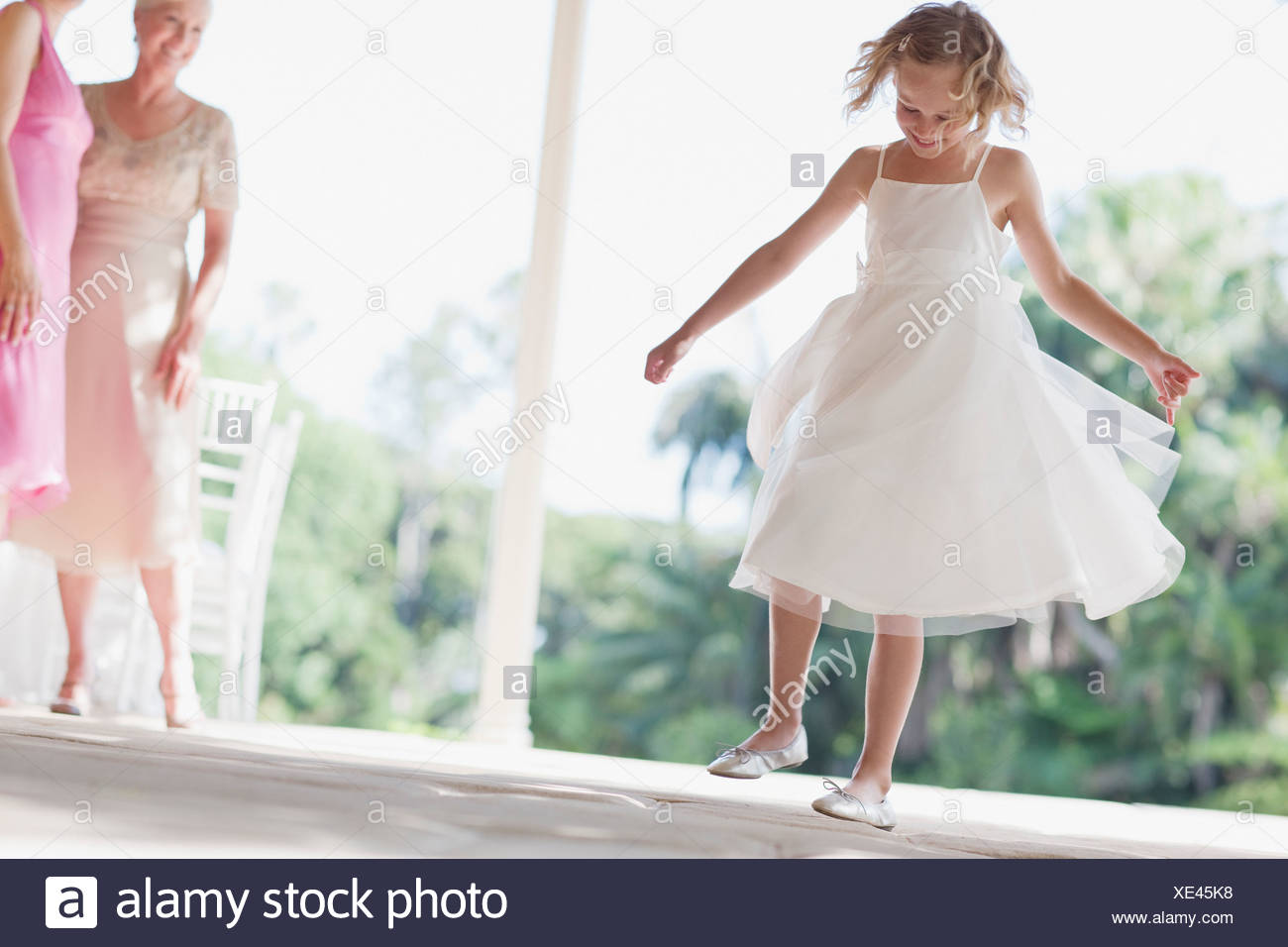 Flower girl playing at wedding reception - Stock Image