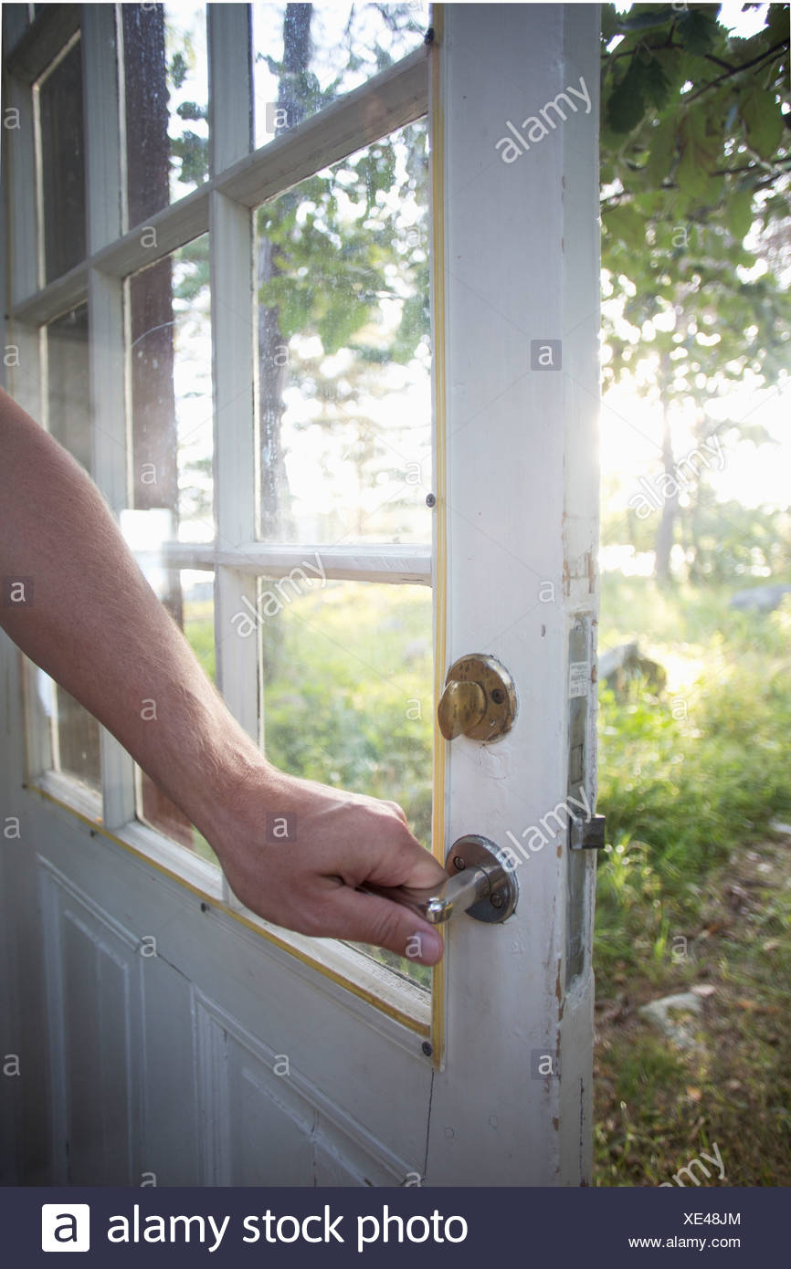 Cropped image of man holding door handle - Stock Image