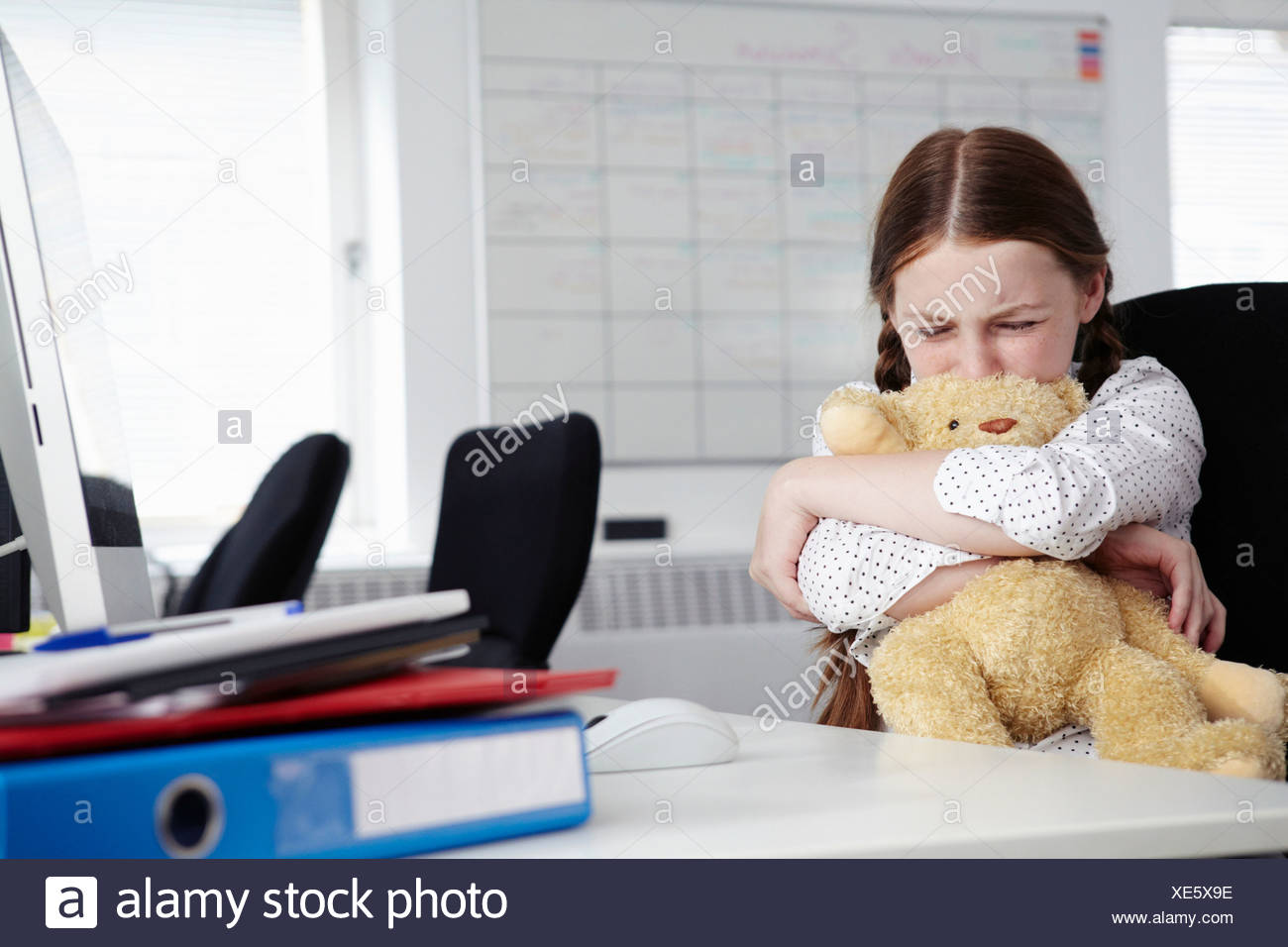 Girl sitting in office hugging teddy bear and crying - Stock Image