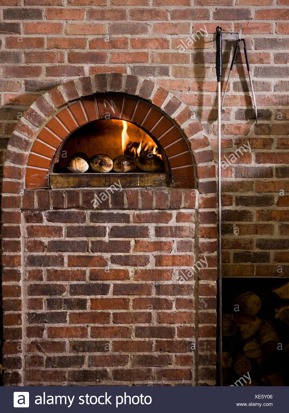 USA, Utah, Orem, logs by brick fireplace - Stock Image