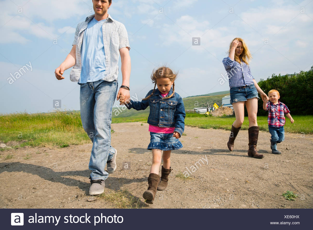 Family walking on rural dirt road - Stock Image