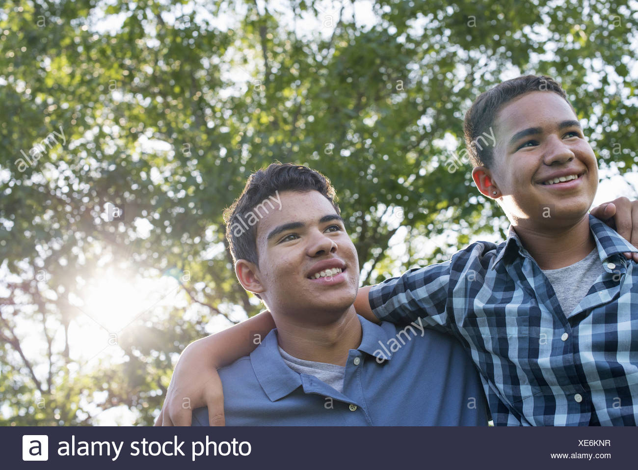 Two young men outdoors one with his arm around the shoulders of the other - Stock Image