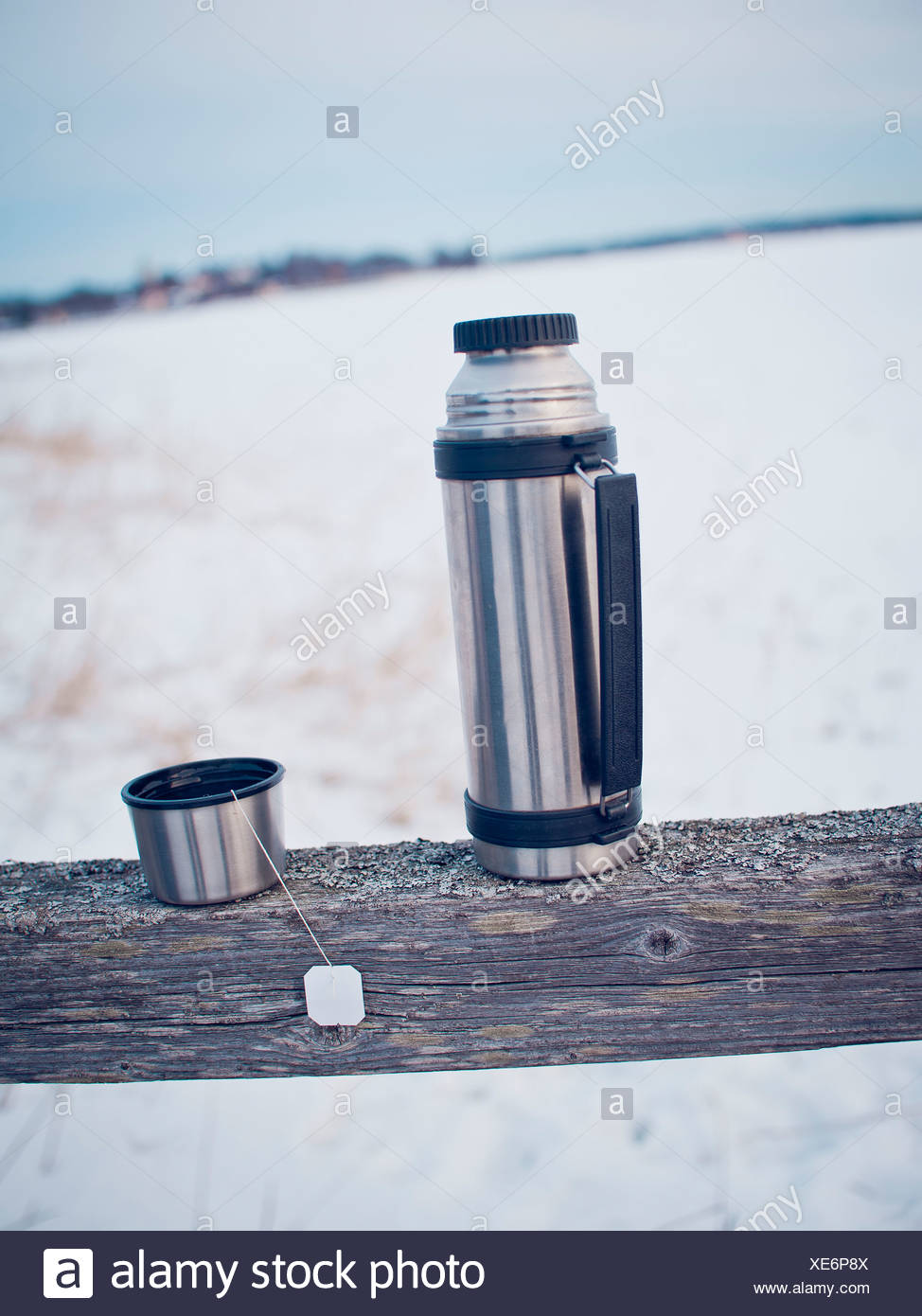 Silver thermos on wooden plank - Stock Image