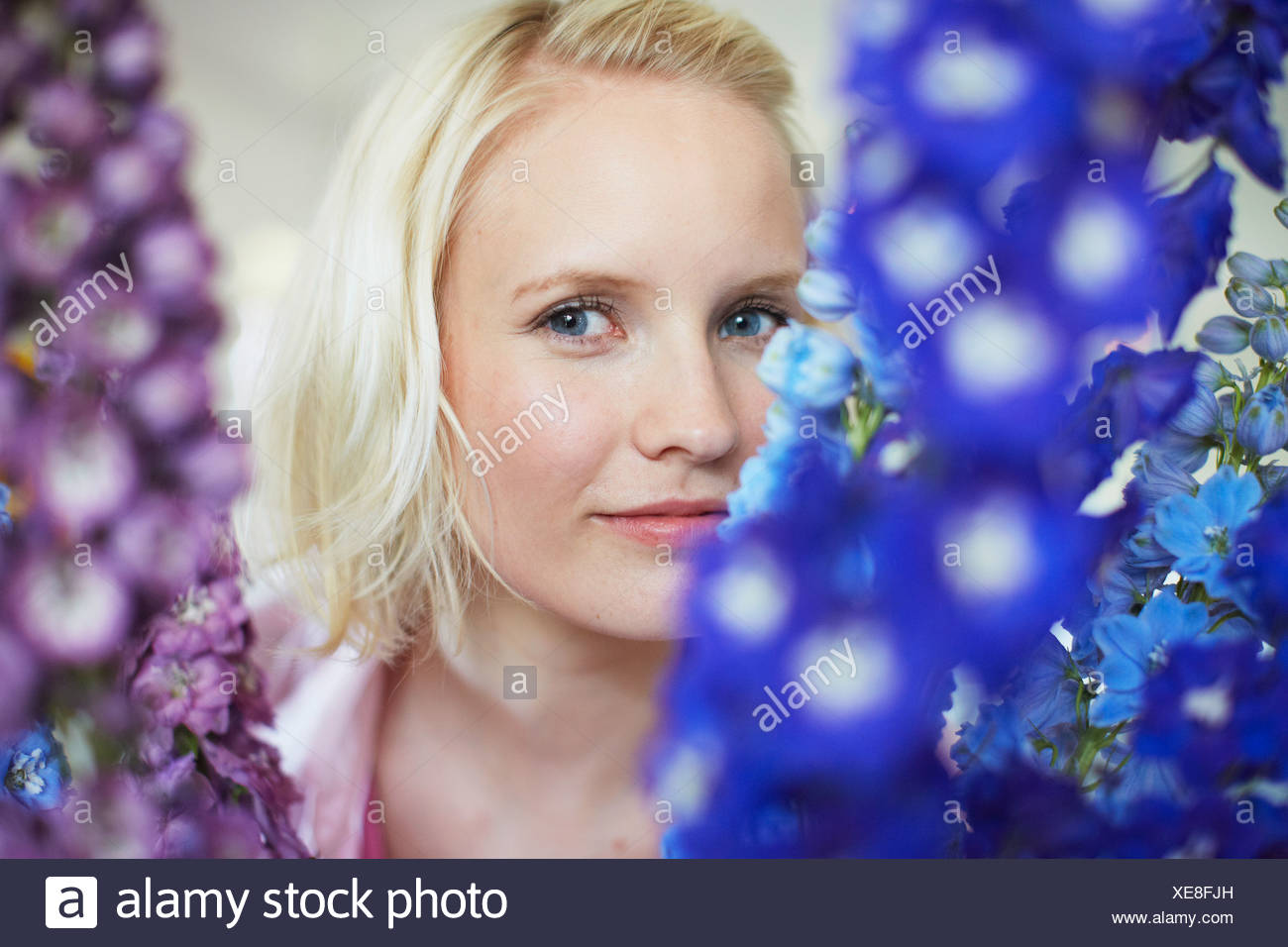 Close up of woman with tall flowers - Stock Image