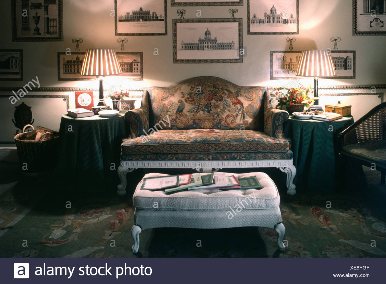 Merveilleux Upholstered Stool In Front Of Antique Sofa In Livingroom Room With Lighted  Lamps And Pictures On The Walls