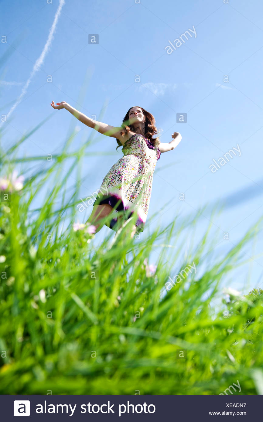 young woman running through grass in park - Stock Image