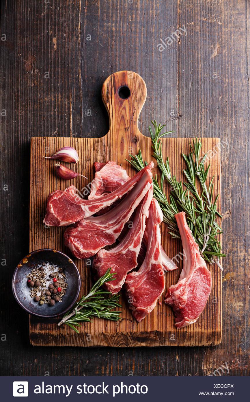 Raw fresh Lamb Meat ribs and seasonings on dark wooden background - Stock Image