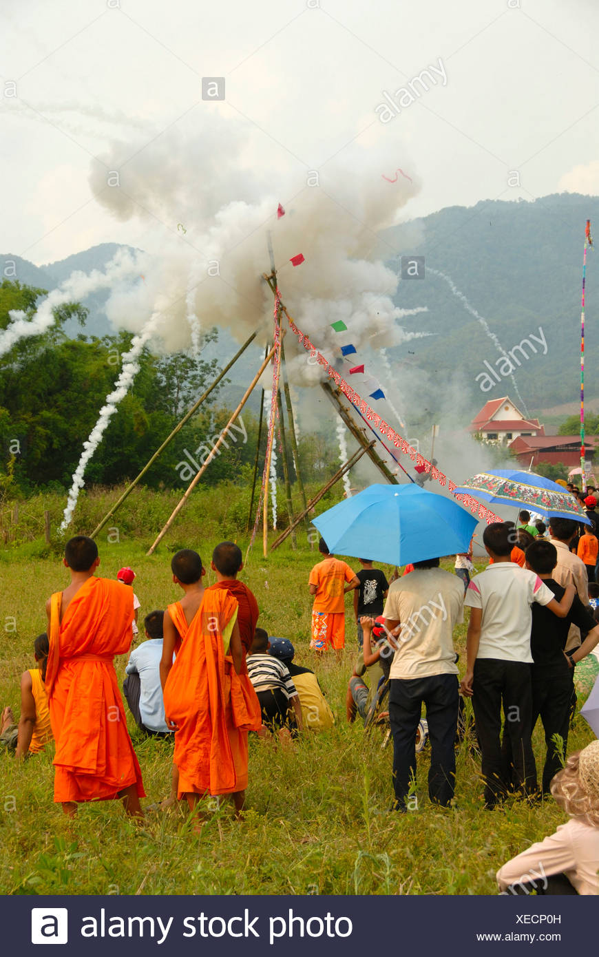 Festival, rocket firing, bang fai, launch and explosion of a rocket on the launch pad, monks in orange robes looking on - Stock Image