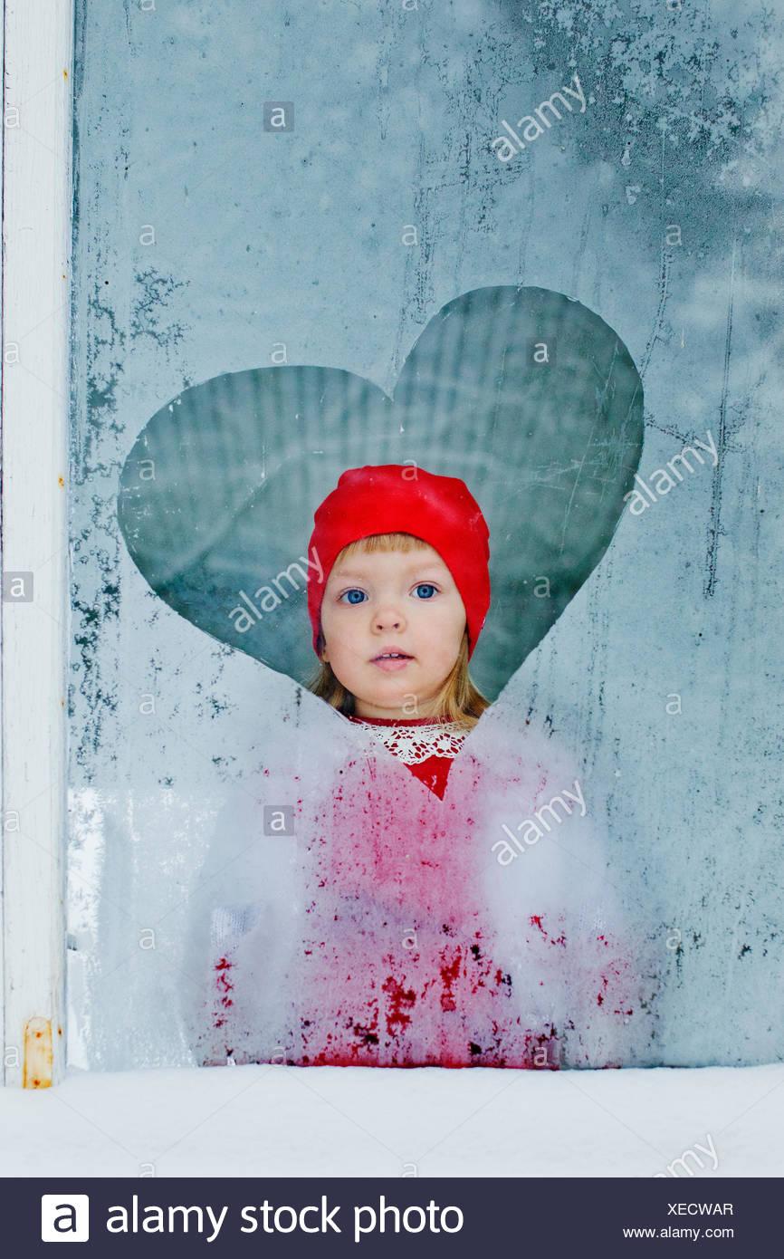 Portrait of girl (4-5) looking through frozen window - Stock Image