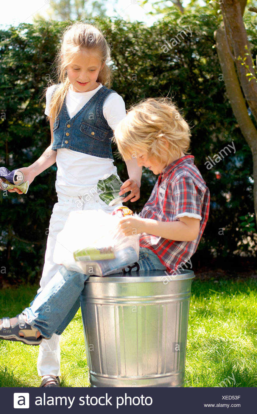 Boy and girl with empty cans, Den Haag, Netherlands - Stock Image