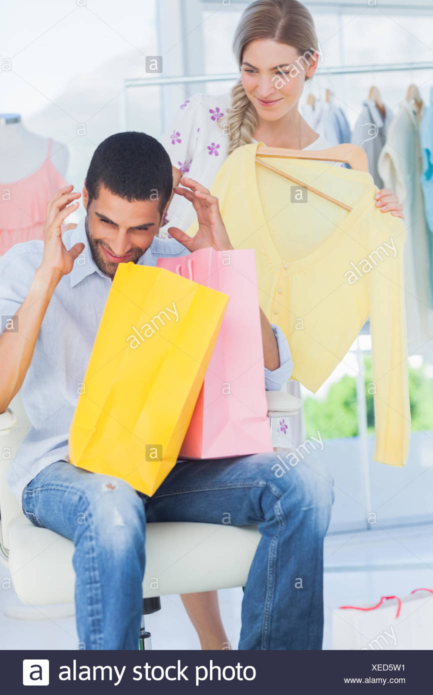Angry man while his girlfriend is shopping - Stock Image