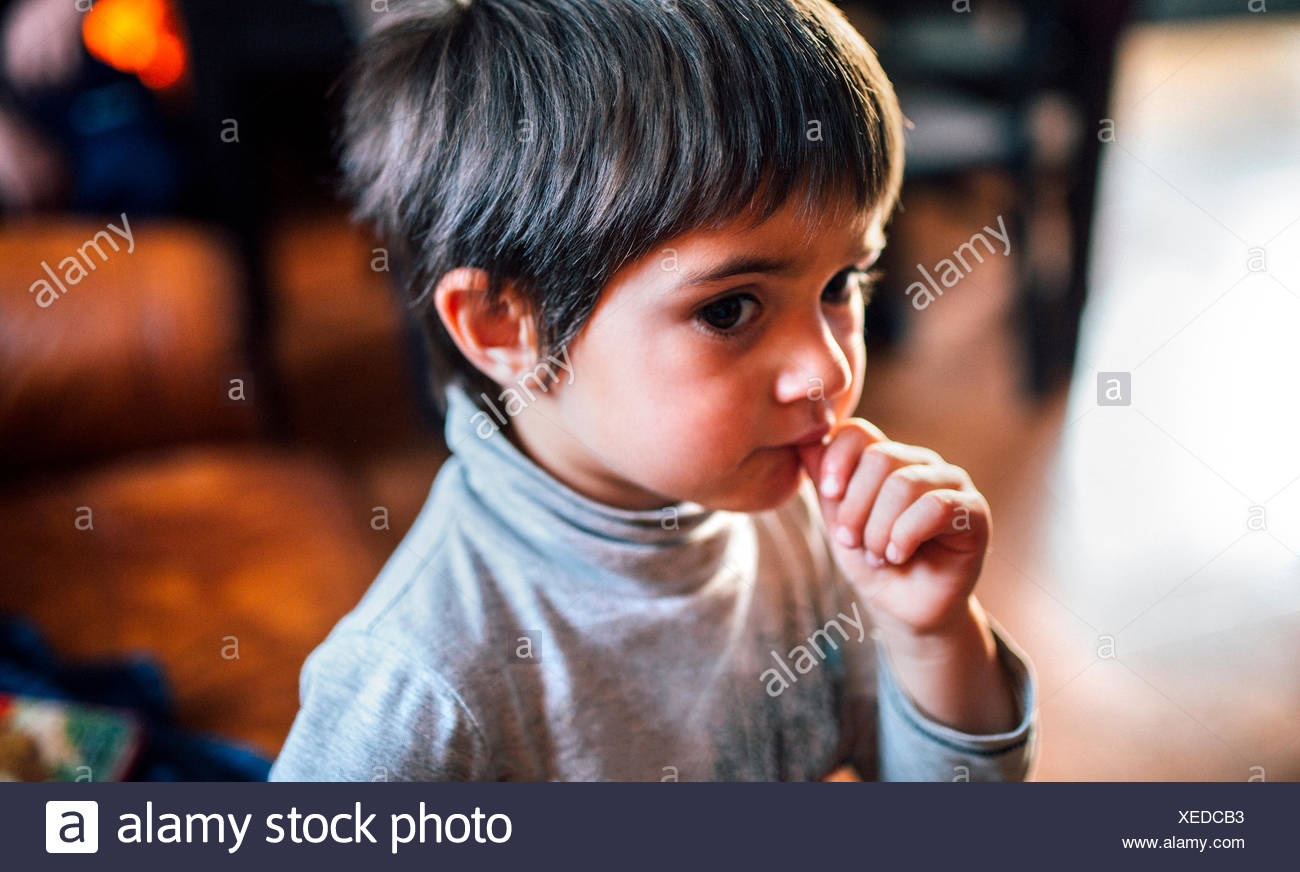 Portrait of little boy with finger in his mouth - Stock Image