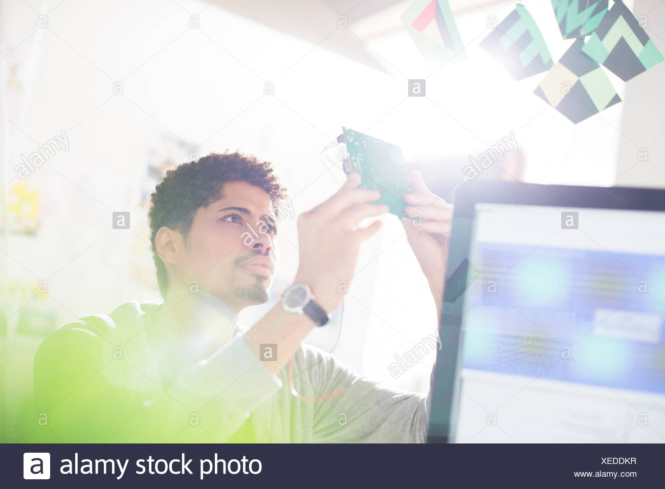 Curious businessman examining part in office - Stock Image
