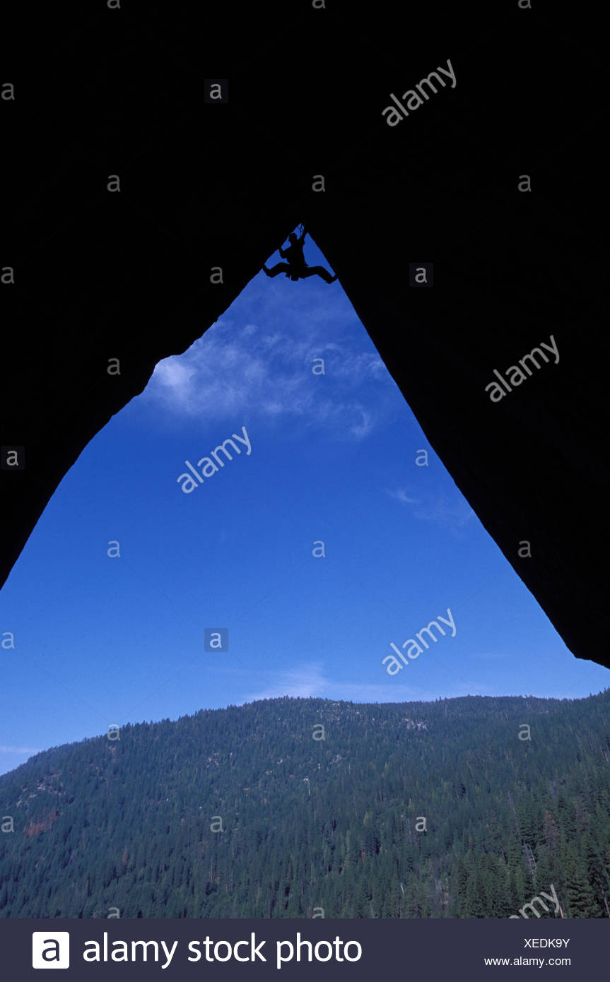 Silhouette of a climber at the top of an overhang. - Stock Image